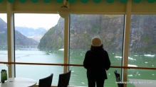 A lady overlooking the window with ice floating on the river.   Photo taken last May 20, 2014 on our way to Sawyer Glacier, Juneau, Alaska