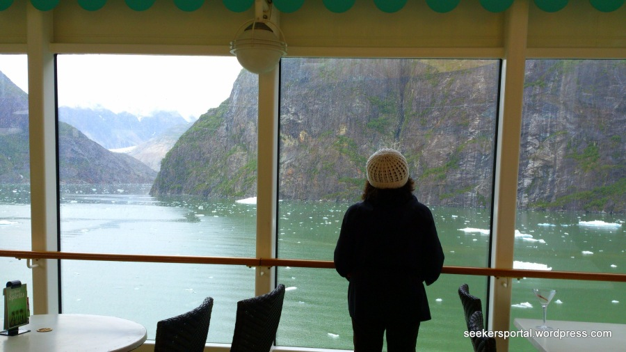 A lady looking at the window with ice floating on the river.  Photo taken last May 20, 2014 on our way to Sawyer Glacier, Juneau, Alaska