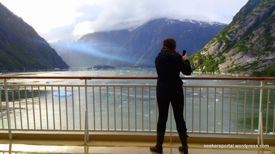 A lady taking photos with her cellphone of the ice-cold surroundings of Sawyer Glacier, Juneau, Alaska